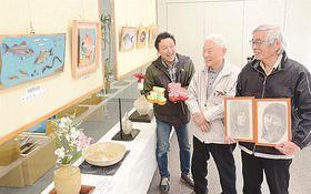 作品を手にする左から永井淳一さんと島谷幸吉さん、川上真人さん=松江市御手船場町、しまね信用金庫本店