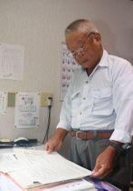「建設は地元と同意の上で着手する」する旨の県との覚書の写しに目を落とす岩本さん=川棚町岩屋郷