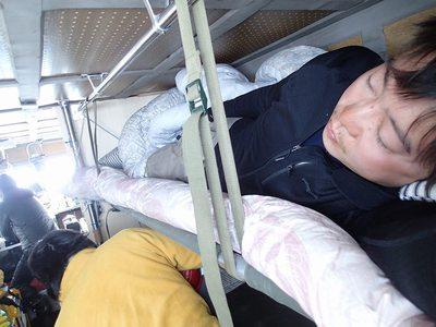 雪上車内で寝る筆者(右上)