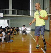 左脚の義足を見せ、生き方を話す山本篤さん(右)=浜松市浜北区の北浜小学校で