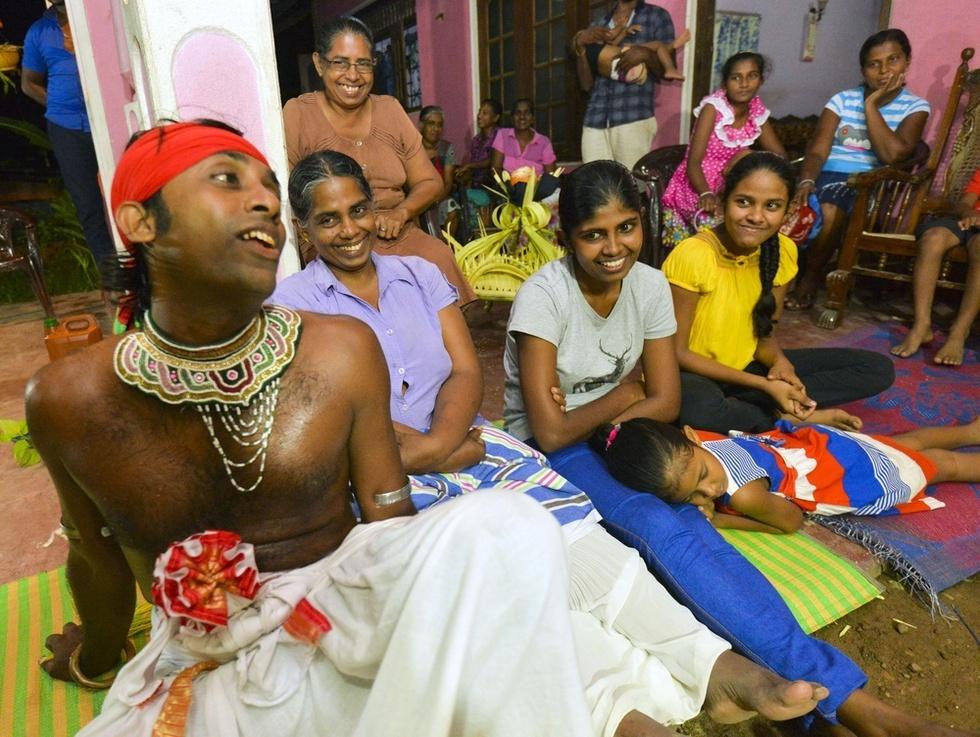 悪魔払いの儀式で、ニプル(左端)と呪術師とのやりとりに笑顔を見せるクムドゥニ(左から2人目)ら家族=スリランカ南部ヒッカドゥワ(撮影・村山幸親、共同)