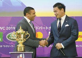優勝杯「ウェブ・エリス・カップ」を台に置き、元南アフリカ代表のブライアン・ハバナさん(左)と握手する五郎丸歩選手=12日、東京都千代田区で