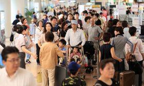 台風10号の接近のため予定を早めたUターン客らで混雑する宮崎ブーゲンビリア空港=13日午前、宮崎市