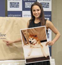 愛犬マサルの写真を手に笑顔のアリーナ・ザギトワ選手=10月4日、さいたま市