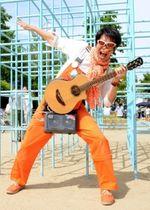 オレンジの衣装にギター片手でダンスや歌を披露する「須磨のスター」しんごお兄さん=須磨区南町1、稲葉公園