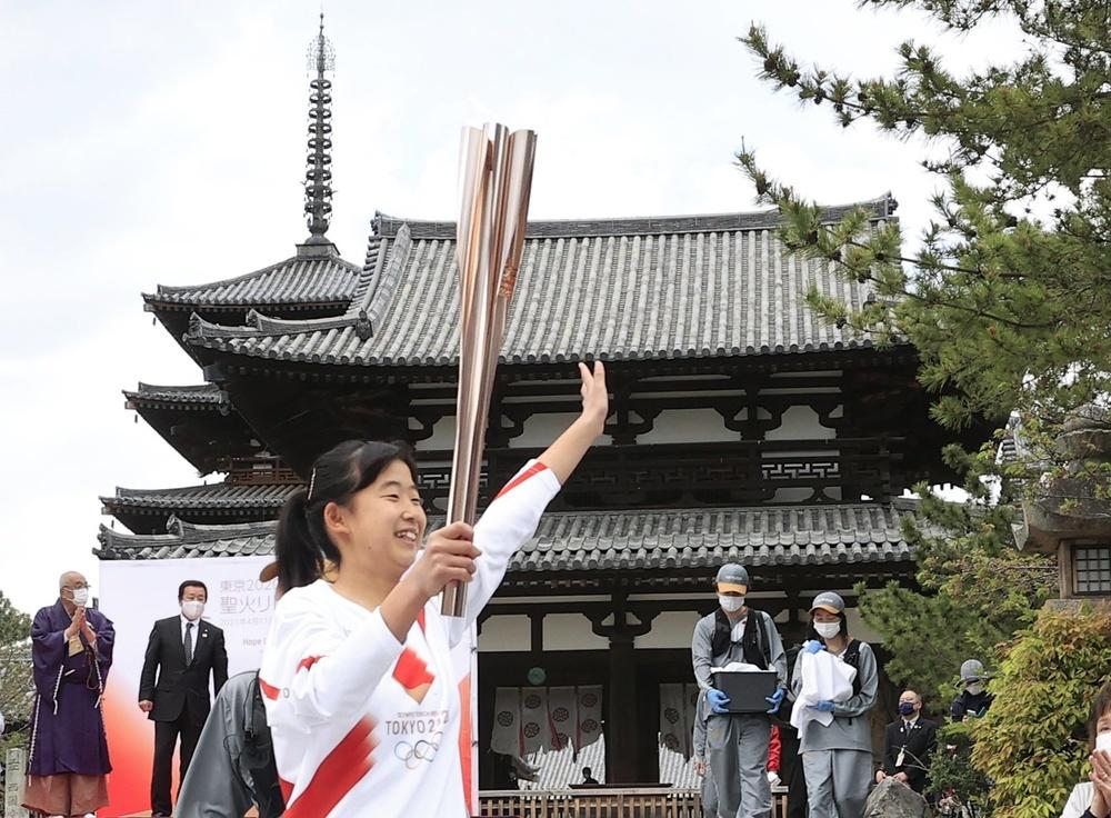 世界最古の木造建築とされる奈良県斑鳩町の法隆寺で、聖火のトーチを掲げて走るランナー=12日午後