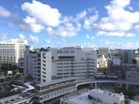 青空の下の那覇市内。ちょうど空港向けのゆいレールが県庁前駅を発車したところです。