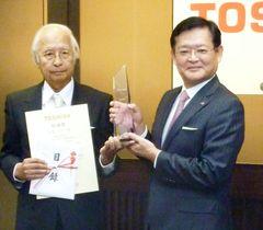 東芝の特別賞を受賞した水島公一エグゼクティブフェロー。右は車谷暢昭会長=19日、東京都港区