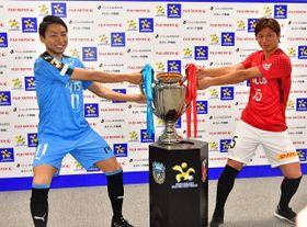優勝カップを奪い合うポーズを取る川崎・小林(左)と浦和・長沢=都内