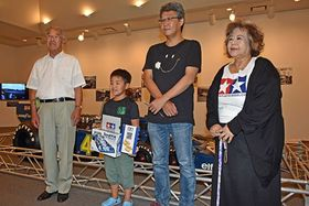 1万人目の来館者となった陽太君(左から2人目)と三浦さん(同3人目)親子。記念写真に納まる新谷理事長(左)と鷹山館長(右)