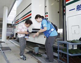 豪雨被害を受けた「まび記念病院」が、移動診療車で試験的に再開した診療を受けに訪れた女性(左)=18日午後、岡山県倉敷市真備町地区