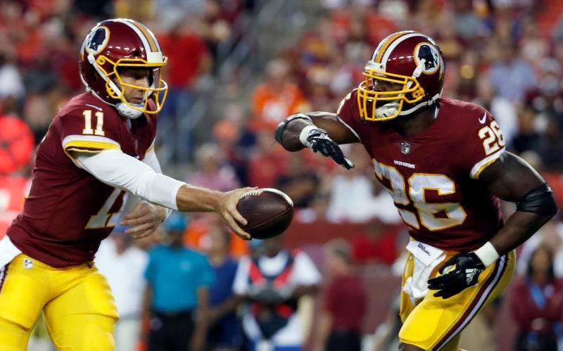 レッドスキンズのQBスミス(左)からボールを手渡されるRBピーターソン(AP=共同)