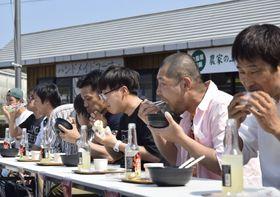 歓声を浴びながら、早食い競争にチャレンジする参加者(四万十町の「あぐり窪川」)