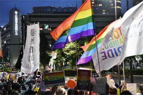 7月、LGBTのシンボルカラー、虹色の旗を掲げ、自民党本部前で抗議活動をする人たち=東京・永田町