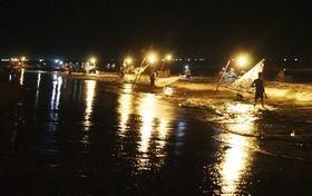 カンテラの明かりが揺らめく海岸に並んでシラスウナギを網ですくう男たち=4月、インドネシア・ジャワ島プラブハンラトゥ郊外(共同)