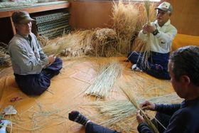 世間話をしながらわらを編み、「つと」を作る住民=五島市上大津町