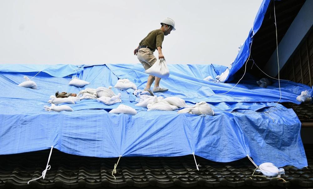 瓦が崩れた屋根にブルーシートをかける男性=25日午前、新潟県村上市
