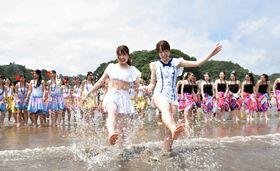 波打ち際で水しぶきを上げるサンシャインガイドいわきと高校生=いわき市・勿来海水浴場