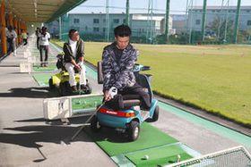 施設内に常備されているカートを使い、練習に励む大村さん(手前)と藤田さん(手前から2人目)=春日井市の春日井グリーンゴルフで