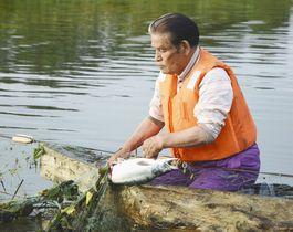 網にかかった魚を回収するアイヌ民族の畠山敏さん=1日、北海道紋別市で
