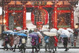 雪が降る中、東京・浅草寺の雷門前を歩く観光客ら