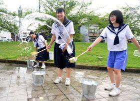 勢いよく水をまいて暑さを和らげる宇多津中生徒ら=宇多津町役場前