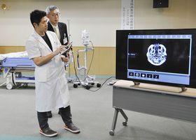 「遠隔画像診断治療補助システム」を使った訓練で、患者のMRI画像を専門医がいる遠方の病院へ送信する医師=昨年12月、高萩市で