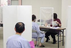 栃木保健福祉センターで、密を避けるため距離を取り、ついたてを隔てて順番を待つ住民検診の受診者。窓も開け放たれている=8月、栃木県栃木市