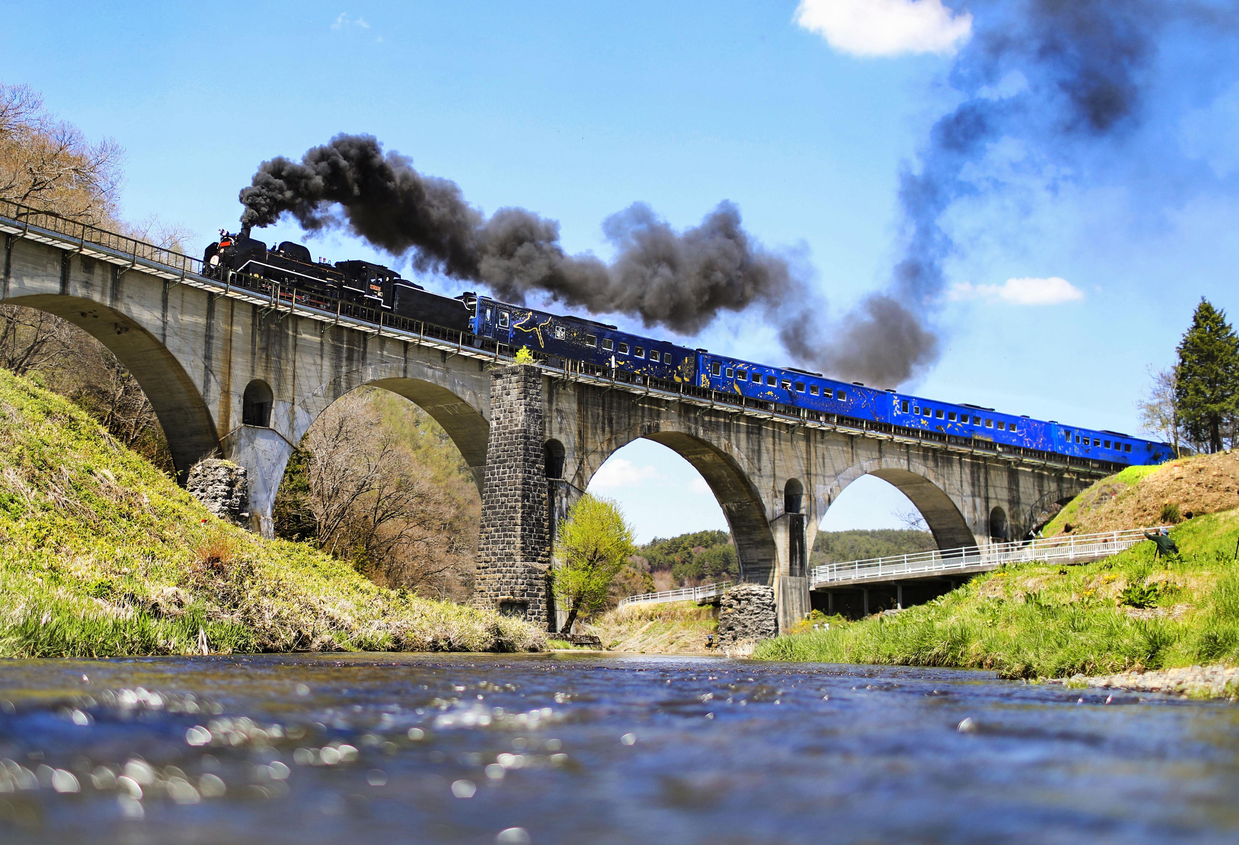 勢いよく煙を上げて、半円が連なるアーチ型の通称「めがね橋」を駆け抜ける蒸気機関車「SL銀河」=岩手県遠野市
