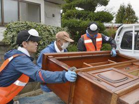 台風19号の大雨で被災した住宅から家具を運び出し、トラックに積み込むボランティア=15日午後、長野県千曲市