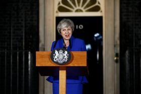 16日、内閣不信任案の否決を受け英首相官邸前で発言するメイ首相(ロイター=共同)