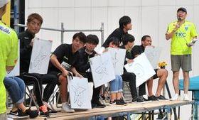 ステージイベントでサポーターと交流する栃木SCの選手たち=宇都宮市馬場通り4丁目