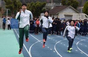 スキップによる短距離走の練習法を子どもたちに伝える白砂さん(左)