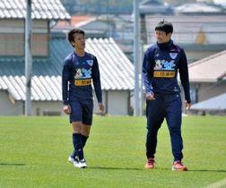 佐賀県鳥栖市内の練習場で鳥栖の高橋秀(右)と談笑する松岡