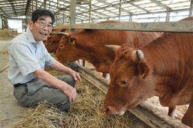 肥育しているあか牛に餌をやる井信行さん=4日、産山村