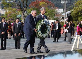 平和祈念像前で献花する(中央右から)白石氏とブルックス氏=長崎市、平和公園