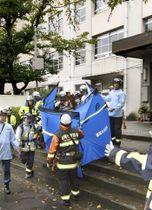 福岡市南区の長住小学校で、児童らを搬送する消防隊員=13日午後1時2分