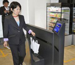実験店舗で、商品の入ったバッグを会計のできる機械に通す女性=19日午後、福岡市