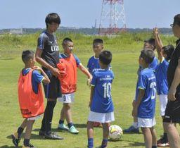 中国のサッカーチームに練習の指示を出すアントラーズアカデミーのコーチ(左から2人目)=潮来市前川