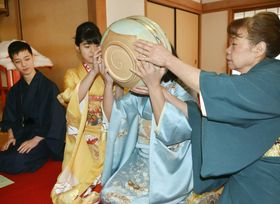 特大茶わんを支えてもらいながら新春の抹茶を味わう参拝者=15日午前、奈良市の西大寺