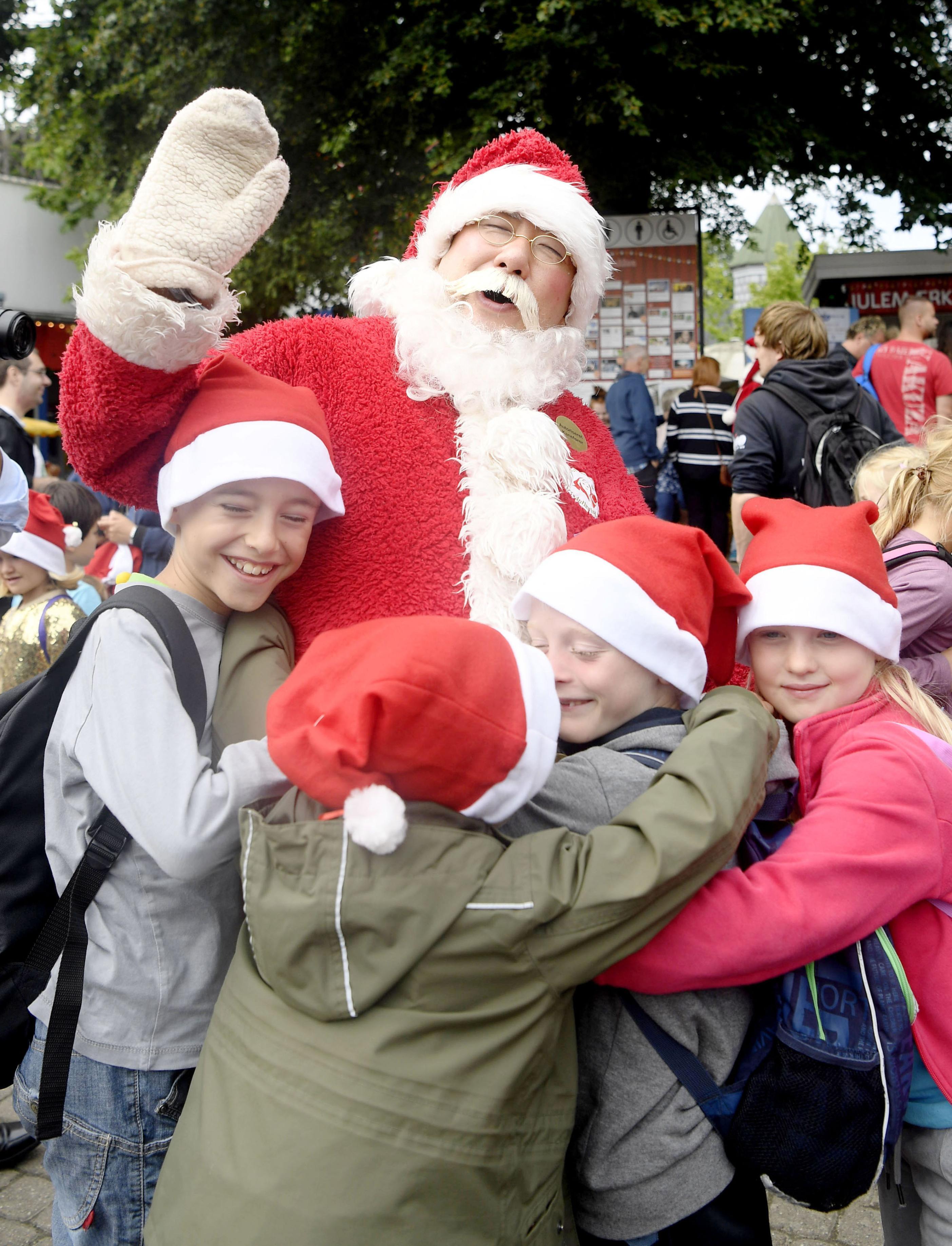 遊園地で子どもたちに抱きつかれるパラダイス山元。「ホッ、ホッ、ホッ」と笑顔で応える=コペンハーゲン郊外(撮影・仙石高記、共同)