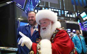"""ニューヨーク証券取引所のトレーダーと、端末を見る""""サンタクロース""""=21日(ロイター=共同)"""