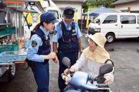 移動交番車(右奥)などが並ぶ駐車場で、警察官と触れ合う高齢者=姶良市北山