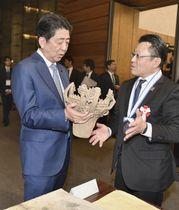 第7回「ものづくり日本大賞」で内閣総理大臣賞を受賞した、大塚オーミ陶業の立体的製陶技術によってつくられた土器の複製を手に持つ安倍首相(左)=22日午後、首相官邸