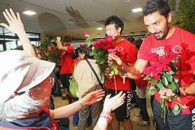 赤いバラの花を手渡しファンを見送る選手ら。右は新メンバーのハン選手(舘山国敏撮影)