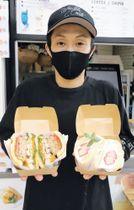 宮城県産食材をたっぷり挟んだパンケーキバーガーをPRする小埜寺社長=つやぱんバーガー E
