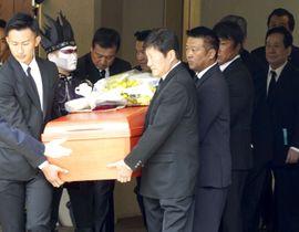 出棺のため車に運ばれる輪島大士さんのひつぎ。左から2人目はデーモン閣下=15日、東京・青山葬儀所