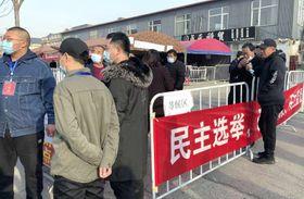 「民主選挙」などと書かれた横断幕が掲げられた村民委選の投票所=4月1日、中国河北省唐山(共同)