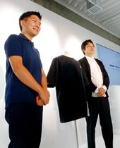 新しい構造タンパク質を素材にしたTシャツの販売を発表する関山和秀代表執行役(左)と渡辺貴生副社長=東京・神宮前