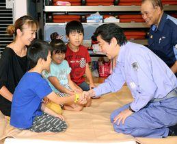 広島県三原市の避難所を訪問し、子どもたちと握手する安倍首相=21日午前(代表撮影)